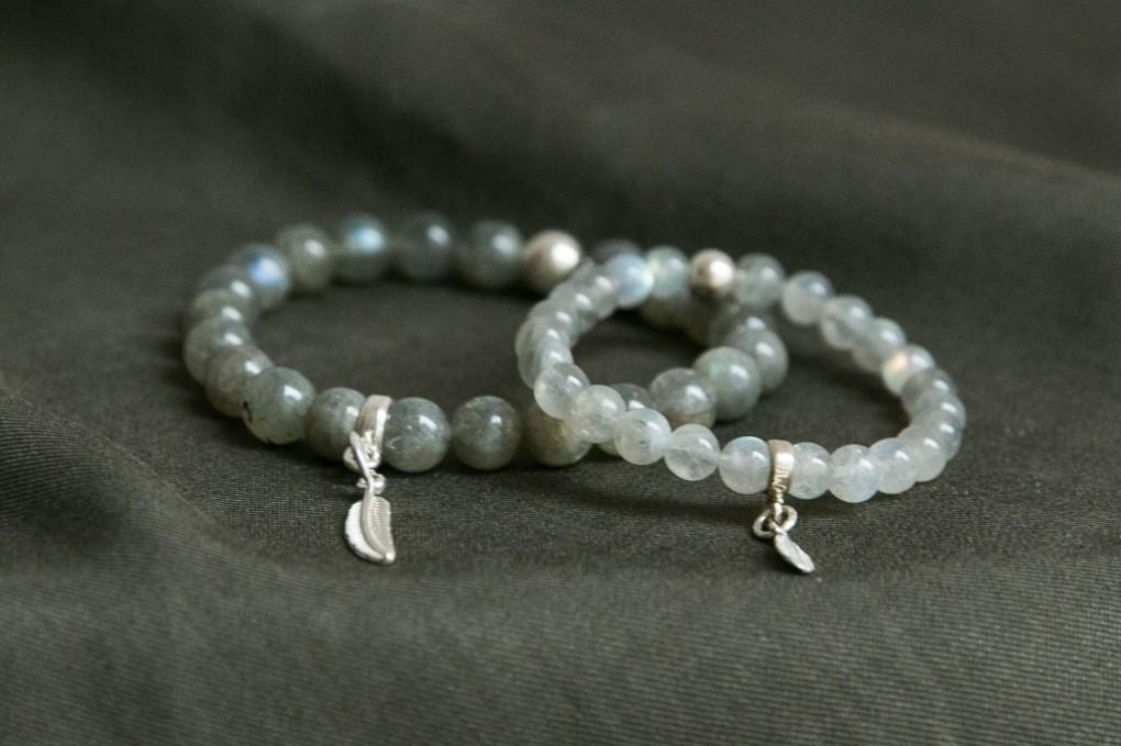"""Refleksyjna Jesień – bransoletki dla mamy i córki to zestaw stworzony ręcznie ze srebra i kamieni naturalnych - labradorytów, nazwanych często """"świątynią gwiazd"""" i symbolizujących entuzjazm, wiarę w siebie i inspirację. To wyjątkowe kamienie, który w promieniach słońca wydobywają swoje wewnętrzne piękno i mienią się kolorami błękitu oraz zgaszonego złota."""